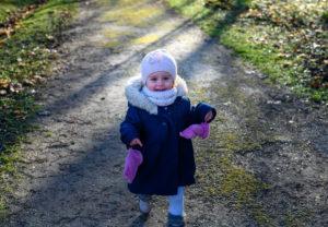 Petite fille en train de courir avec un grand sourire dans la forêt photographe enfant Houilles photographe Houilles
