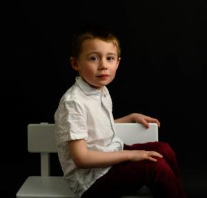 Petit garçon en chemise blanche et pantalon rouge assis sur un banc blanc, fond noir, photographe d'enfants Houilles