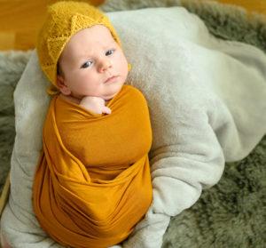 bébé éveillé emmailloté de jaune avec un bonnet jaune dans une caisse, photographe bébé Houilles, photographe nouveau-né Houilles, photographe naissance Houilles