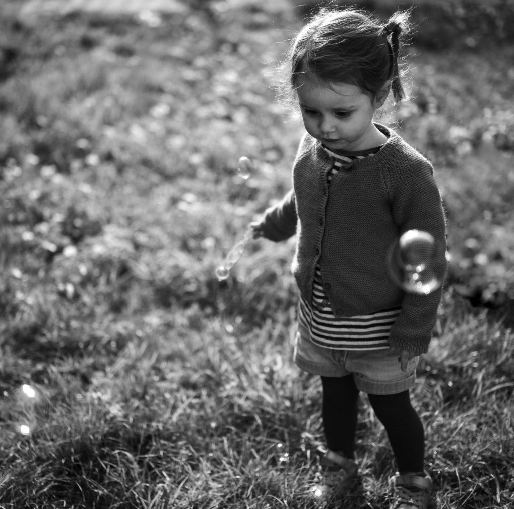 portrait noir et blanc d'une petite fille qui fait des bulles en extérieur photographe enfants Houilles photographie lifestyle Houilles