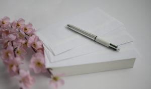 Livre, enveloppes et stylos avec fleur rose  Photographe grossesse Houilles photographe naissance Houilles photographe bébé Houilles photographe enfant Houilles photographe famille Houilles