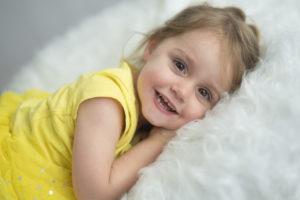 le souriante posée sur un beanbag et couverture aux poils longs blanche Photographe enfants Houilles