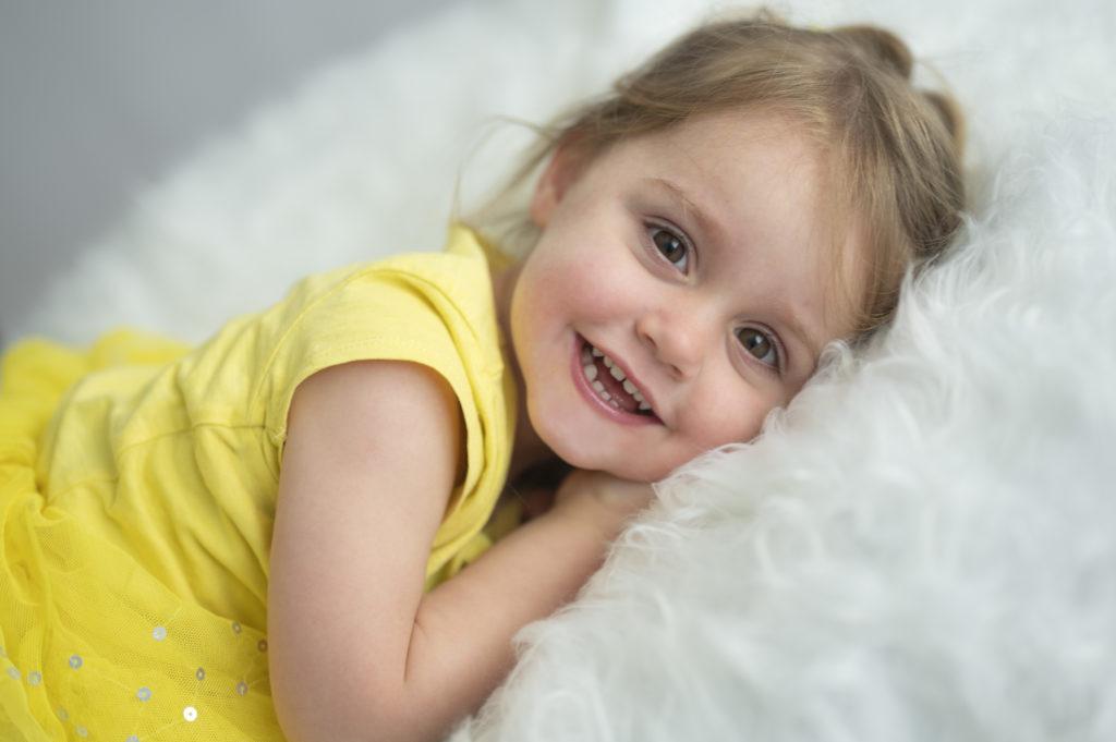 toute petite fille vêtue de jaune allongée sur beanbag photographe enfant Houilles photographe bébé Houilles photographe Houilles
