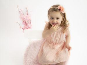 Petite fille en robe rose et bandeau rose fleuri, assise sur un banc auquel des fleurs roses sont accrochées Photographe enfants Houilles