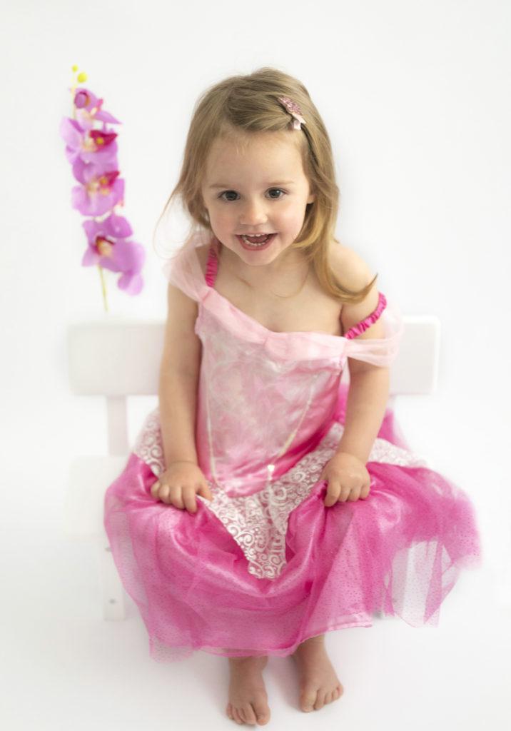 Petite fille en robe de princesse qui éclate de rire, assise sur un banc fleuri Photographe enfants Houilles Photographe Houilles