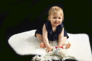 Bébé fille assise sur un tapis blanc, faisant un grand sourire avec doudou dans les mains, photographie de bébé Houilles