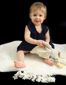 Bébé fille sur fond noir assise sur fourrure blanche Photographe bébé Houilles Photographe bébés Houilles Photographe Houilles