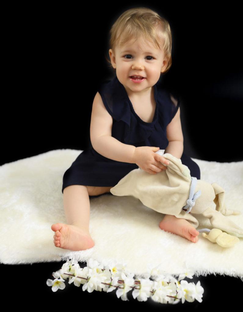 petite fille assise sur une fourrure blanche qui fait un grand sourire photographe bébé Houilles photographe Houilles