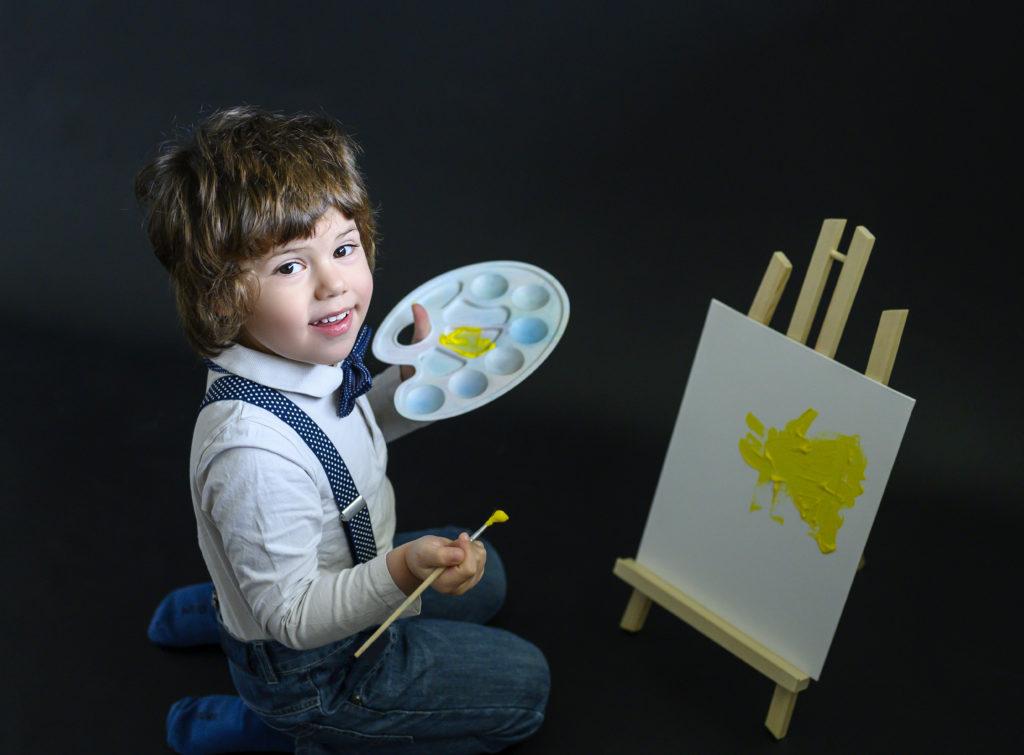 Petit garçon sur fond noir en train de peindre sur un petit chevalet Photographe enfant Houilles Photographe enfants Houilles Photographe Houilles
