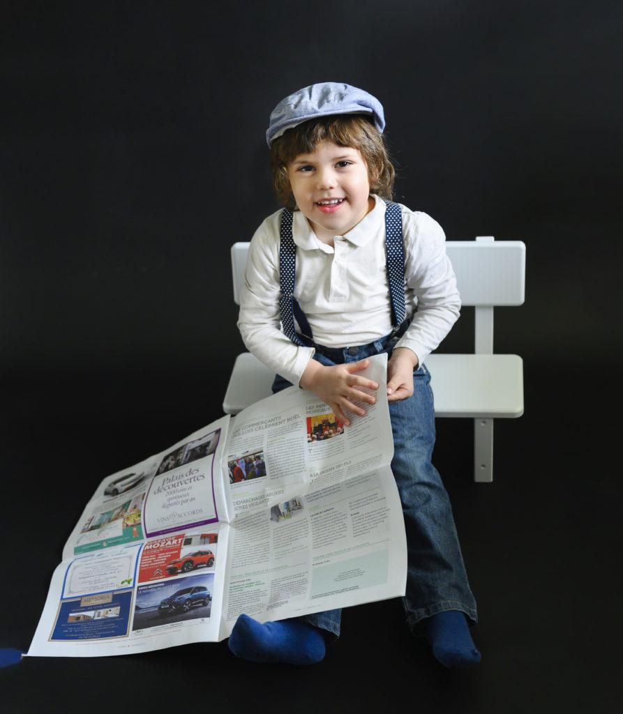 Petit garçon avec un béret et des bretelles lit le journal assis sur un banc  Photographe enfants Houilles Photographe enfant Houilles Photographe Houilles