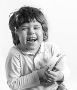 Petit garçon avec un tambourin dans les mains qui rit, portrait noir et blanc, photographie d'enfants Houilles Photographe enfant Houilles Photographe Houilles