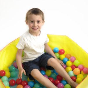 Petit garçon souriant assis dans une piscine à balles Photographe enfant Houilles Photographe enfants Houilles Photographe Houilles