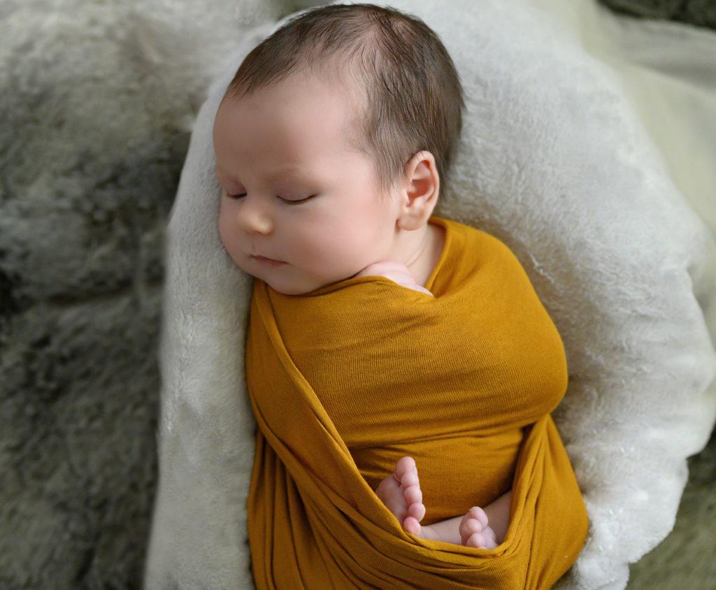 Nouveau-né emmailloté de jaune, endormi dans une caisse