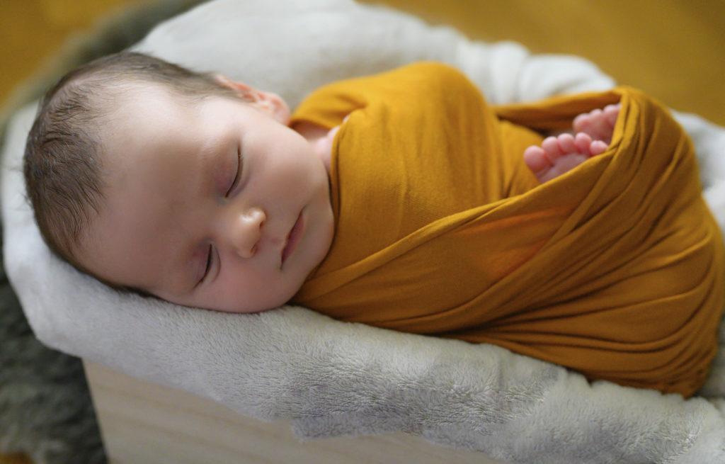 Nouveau-né emmailloté de jaune endormi dans une caisse, photographe nouveau-né Houilles