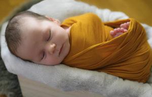 bébé emmailloté de jaune endormi dans une caisse, photographe bébé Houilles, photographe nouveau-né Houilles, photographe naissance Houilles Photographe Houilles