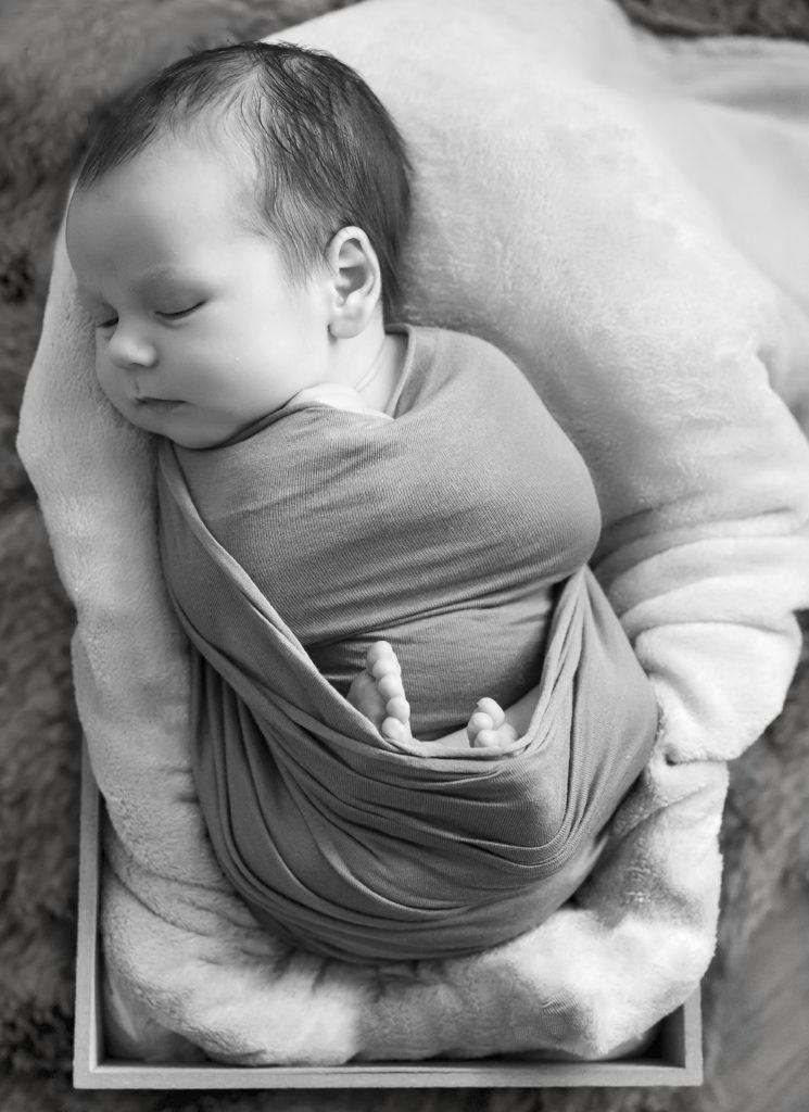 Portrait noir et blanc d'un nouveau-né emmailloté endormi dans une caisse, photographe nouveau-né Houilles