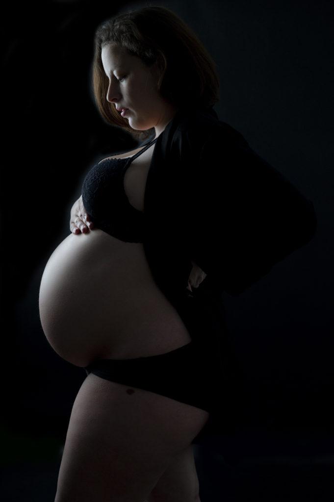 femme enceinte en clair obscur regarde son ventre photographe grossesse Houilles photographe maternité Houilles photographe Houilles