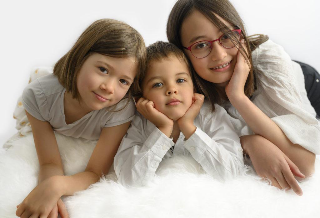 deux soeurs encadrent leur petit frère à plat ventre sur une couverture blanche photographe enfants Houilles photographe famille Houilles photographe Houilles