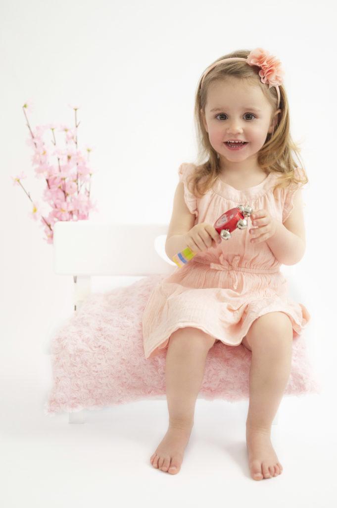 Petite fille vêtue de rose sur mini banc fleuri photographe enfant Houilles photographe Houilles