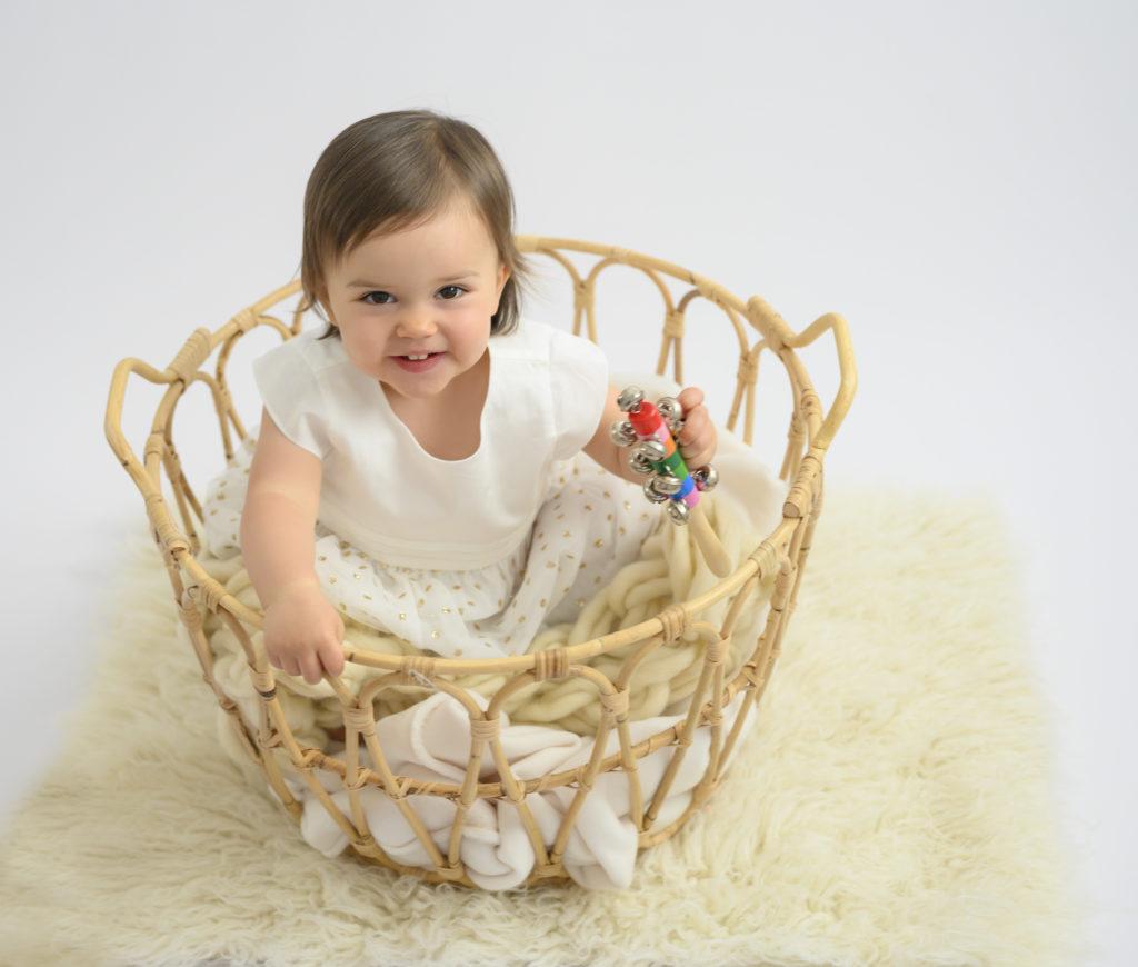 bébé fille tout sourire assise dans un panier sur flokati blanc photographe bébé Houilles photographe sitter Houilles photographe Houilles