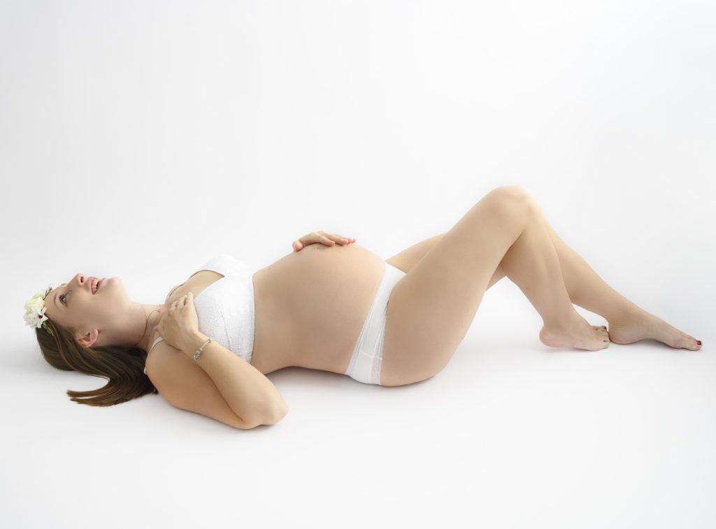 Femme enceinte en dessous blancs et headband fleuri allongée sur le dos photographe grossesse Houilles shooting femme enceinte Houilles photographe maternité Houilles