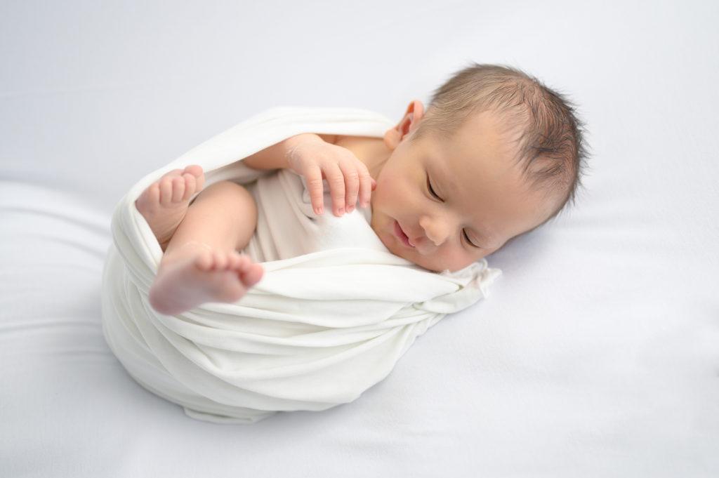 nouveau-né emmailloté bonnet blanc sur beanbag blanc photographe naissance houilles photographe nouveau-né houilles photographe houilles