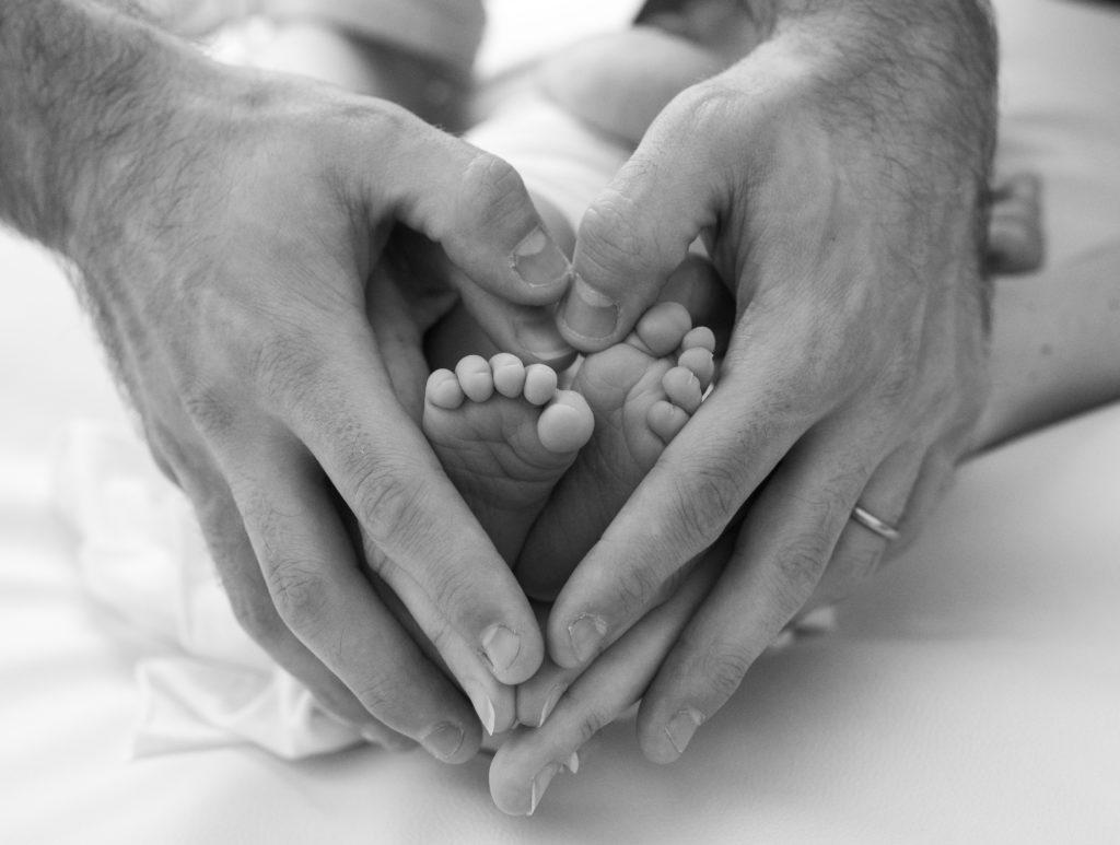 tout petits pieds de nouveau-né dans les mains de ses parents photographe naissance houilles photographe nouveau-né houilles photographe houilles
