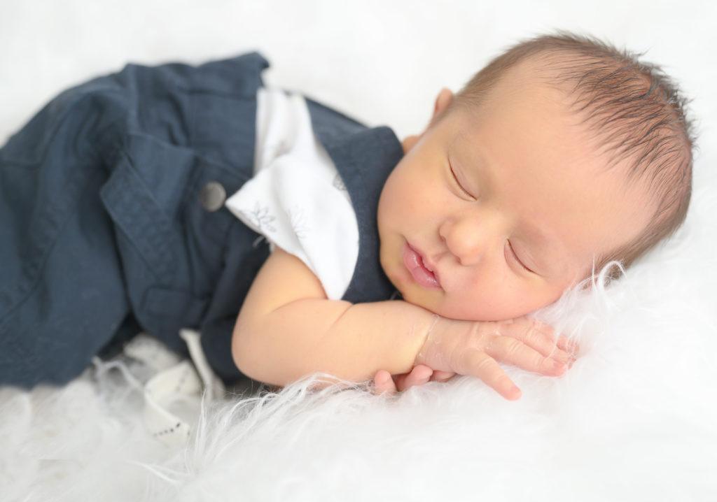 Nouveau né en salopette endormi sur beanbag en pose bump up Photographe naissance Houilles photographe nouveau-né Houilles photographe Houilles