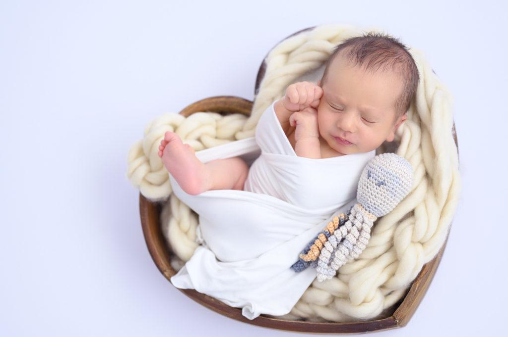 nouveau-né emmailloté dans un contenant en forme de coeur photographe naissance houilles photographe nouveau-né houilles photographe houilles