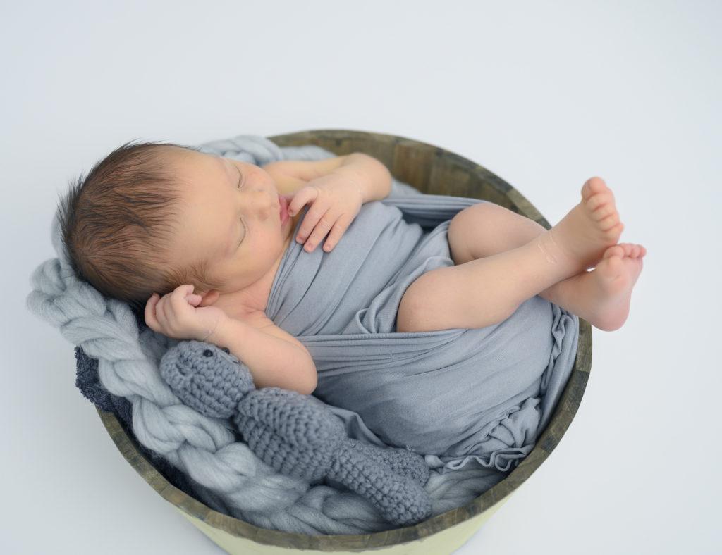 nouveau-né emmailloté de gris dans une terrine ronde en bois tresse en laine grise nounours gris photographe naissance houilles photographe nouveau-né houilles photographe houilles