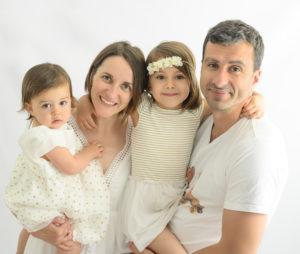 famille vêtue de blanc petite fille et bébé fille dans les bras de leurs parents photographe famille Houilles photographe Houilles