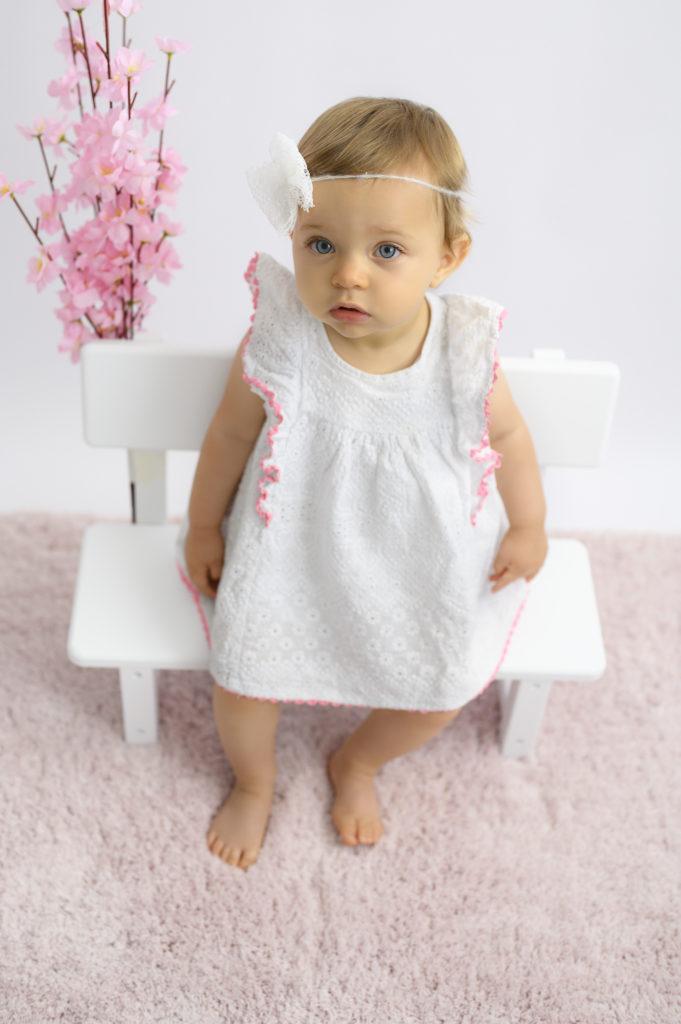 Bébé de 10 mois assise sur un petit banc, robe blanche bandeau blanc fleurs et tapis roses Photographe bébé Houilles photographe Houilles