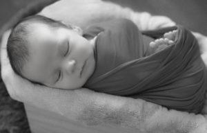 bébé emmailloté endormi dans une caisse photographe naissance houilles photographe nouveau-né houilles