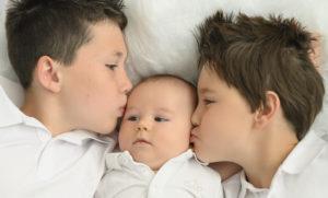 fratrie entourant un bébé allongés sur tapis blanc photographe enfant Houilles photographe bébé Houilles photographe famille Houilles photographe enfant photographe bébé photographe famille