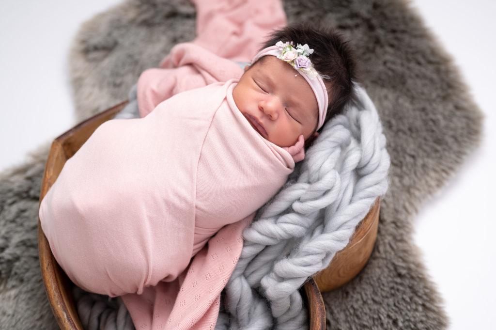 nouvelle née emmaillotée de rose headband rose endormie dans coeur en bois sur tresse en laine grise photographe naissance nouveau-né Houilles Yvelines la Défense