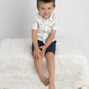 petit garçon souriant assis sur un banc couvert de fourrure blanche photographe famille Houilles photographe enfant Houilles