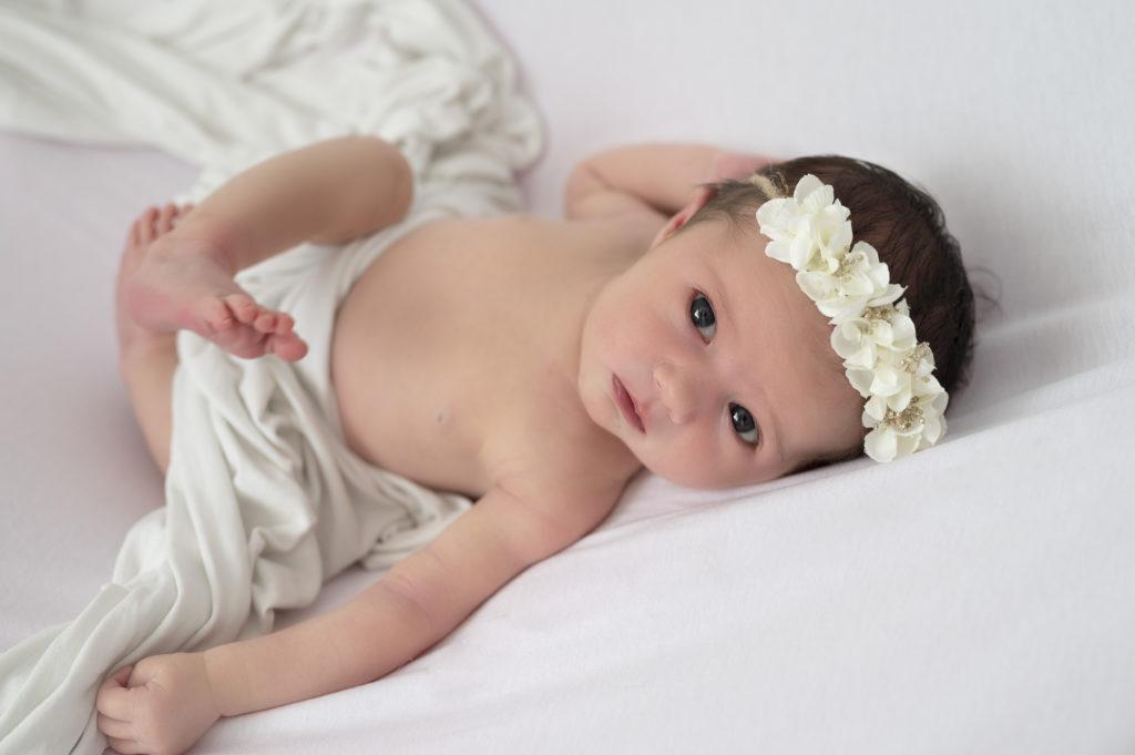 bébé fille headband blanc allongée sur le dos regard objectif  photographe naissance Houilles