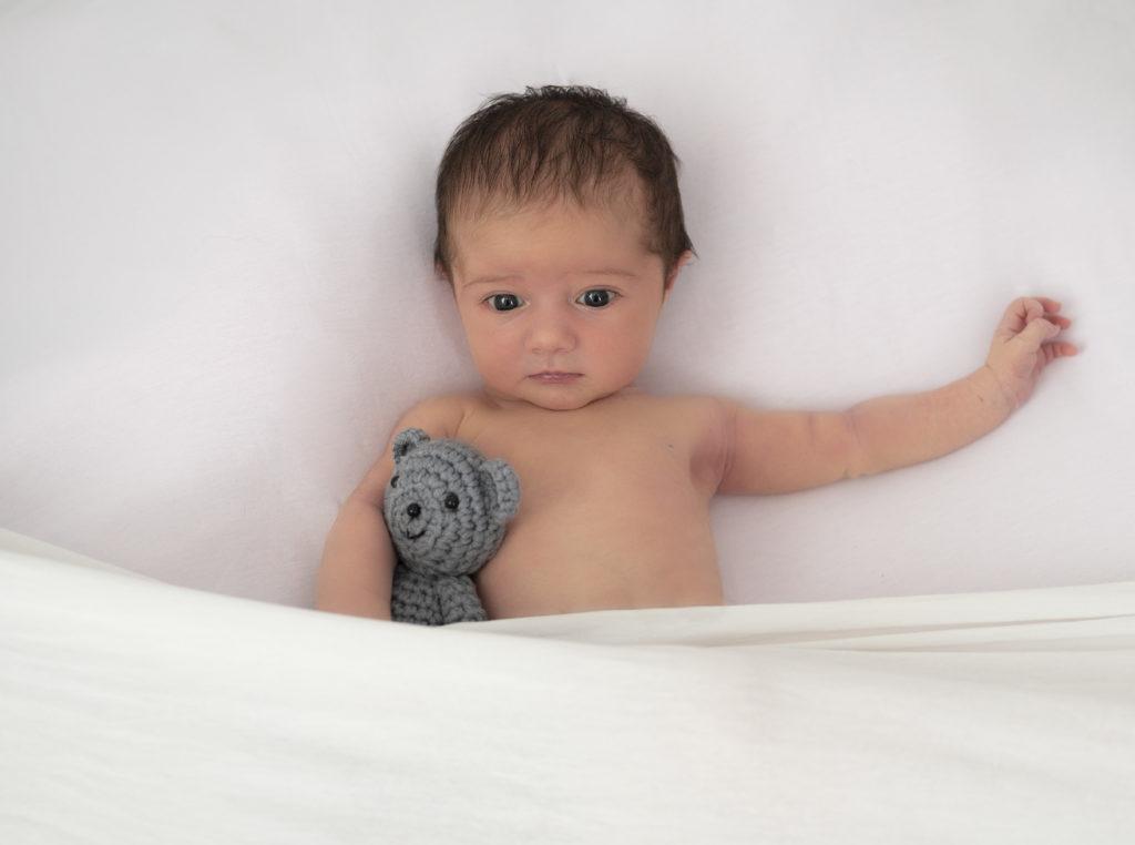 nouvelle née sur beanbag qui tient un petit nounours gris dans ses bras photographe naissance Houilles Yvelines photographe nouveau-né Houilles Yvelines