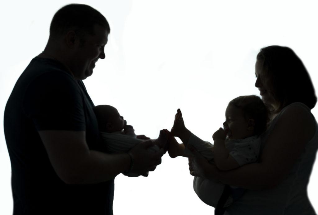 parents qui tiennent leurs bébés dans les bras en contrejour  photographe famille Houilles photographe Houilles