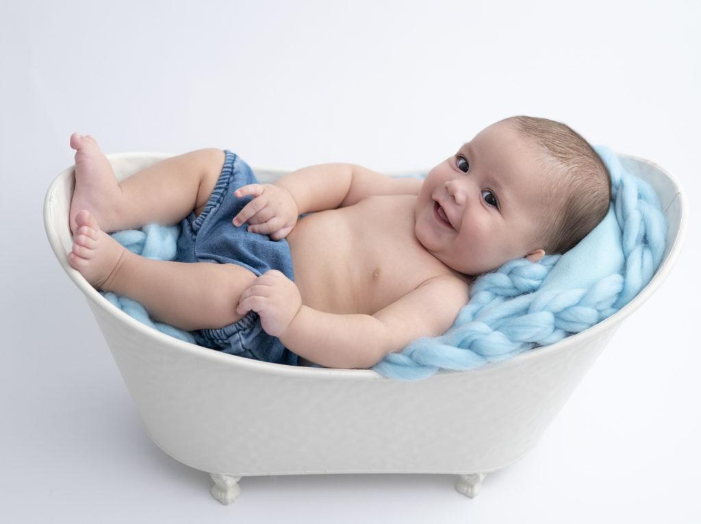 bébé cache couche bleu allongé dans une petite baignoire fait un sourire photographe bébé Houilles photographe Houilles