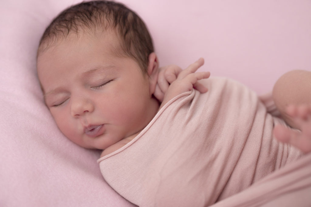 Nouvelle-née emmaillotée de rose, endormie sur beanbag rose photographe nouveau-né Houilles photographe naissance Houilles photographe Houilles Yvelines