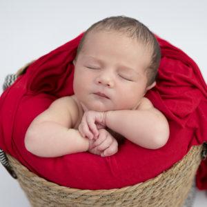 nouveau-né endormi dans un panier avec wrap rouge photographe naissance houilles yvelines