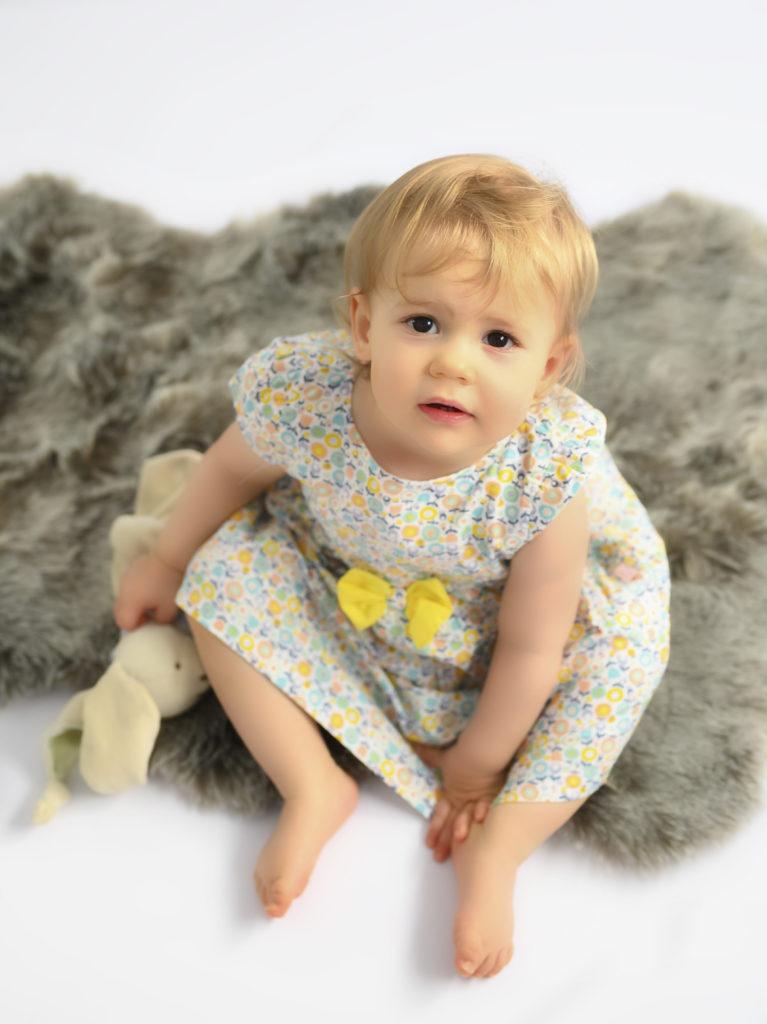 bébé fille de 15 mois assise sur un tapis en fourrure grise lève la tête photographe bébé Houilles photographe Houilles