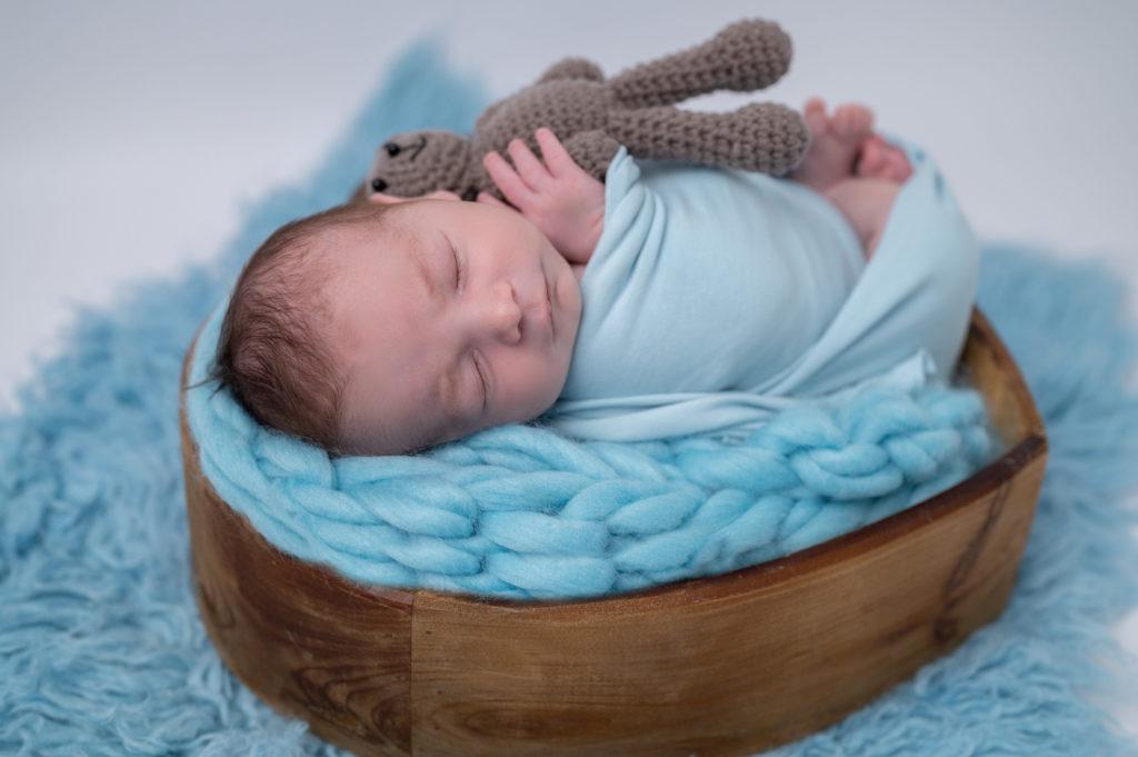 nouveau-né emmailloté de bleu endormi dans coeur en bois sur tresse en laine bleue photographe naissance nouveau-né houilles yvelines la défense