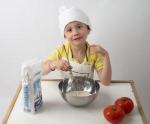 petit garçon avec une toque et un tablier blanc en train de cuisiner photographe enfant Houilles Yvelines la Défense