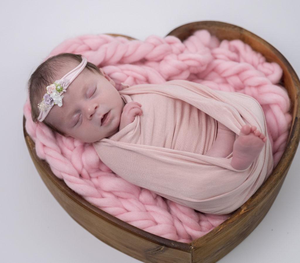 bébé emmaillotée de rose endormie dans coeur en bois sur tresse en laine rose photographe naissance nouveau-né houilles yvelines la défense