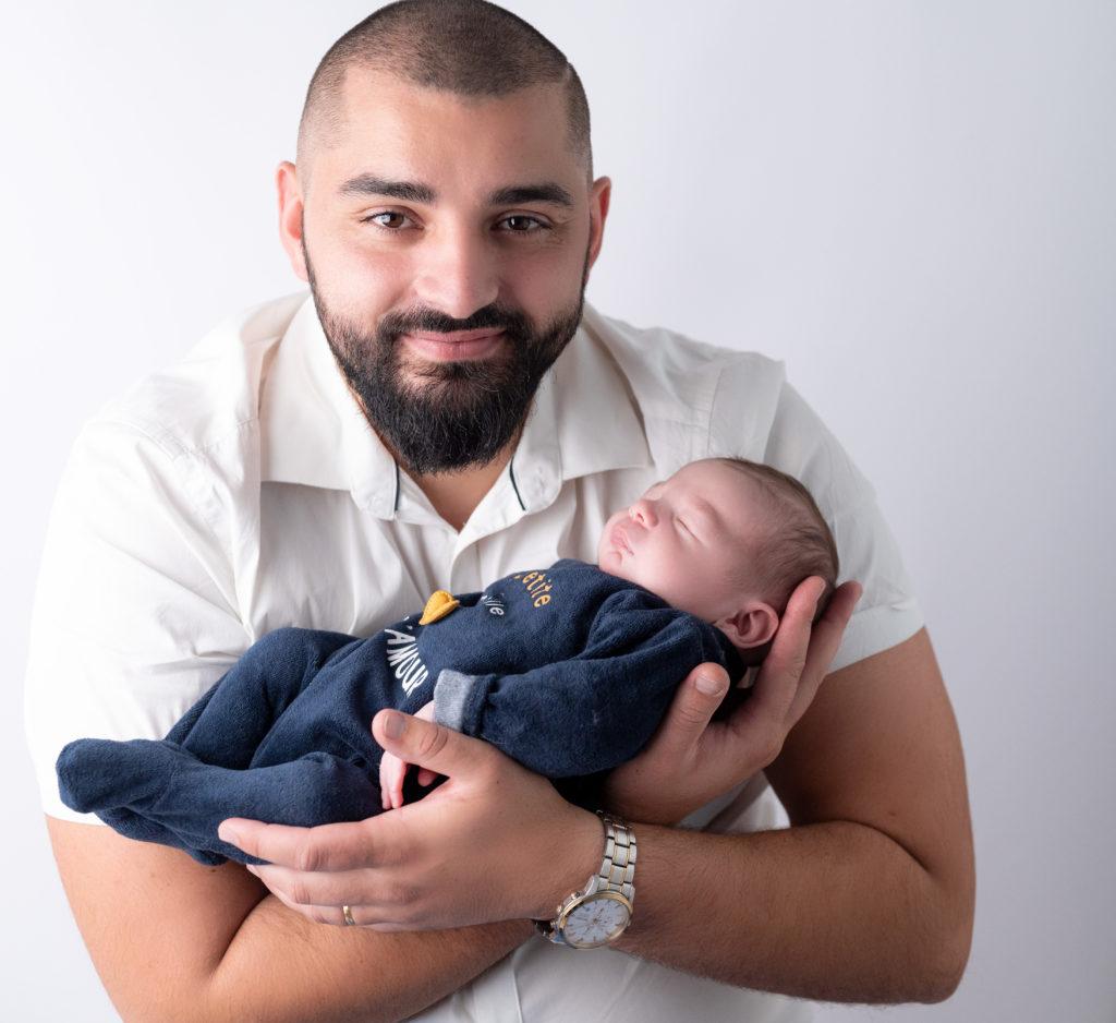 jeune papa tenant son nouveau-né dans les bras photographe naissance Houilles Yvelines la Défense