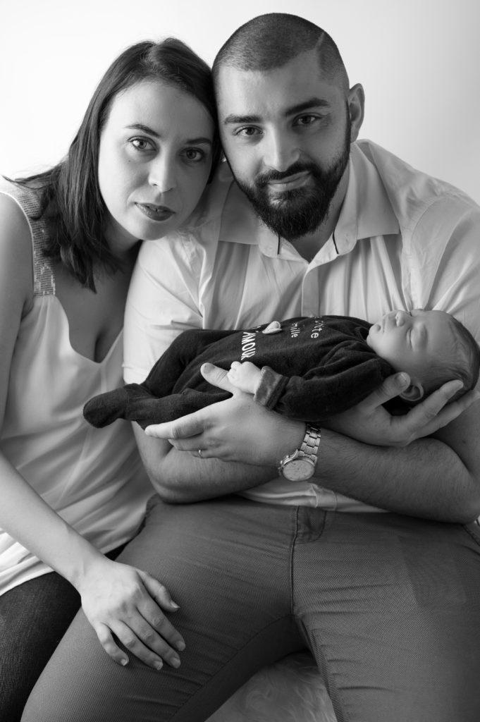 portrait noir et blanc de jeunes parents tenant leur nouveau-né de 11 jours photographe naissance nouveau-né Houilles Yvelines la Défense