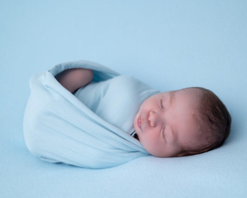 nouveau-né emmailloté de bleu endormi sur beanbag photographe naissance nouveau-né Houilles Yvelines la Défense