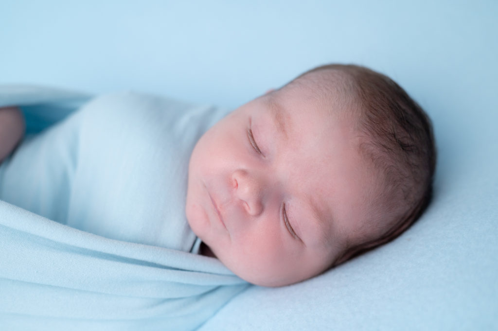 portrait en gros plan d'un nouveau-né emmailloté de bleu endormi sur beanbag photographe naissance nouveau-né Houilles Yvelines la Défense